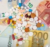 Pieniądze i pigułki Pigułki różni kolory na pieniądze pojęcie kłama medycyny pieniądze ustalonego stetoskop Euro gotówka Fotografia Royalty Free