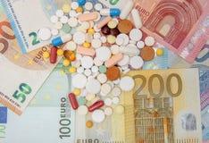Pieniądze i pigułki Pigułki różni kolory na pieniądze pojęcie kłama medycyny pieniądze ustalonego stetoskop Euro gotówka Fotografia Stock