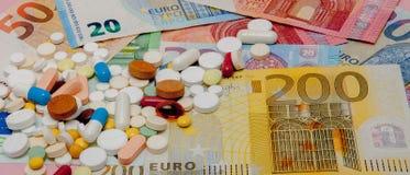 Pieniądze i pigułki Pigułki różni kolory na pieniądze pojęcie kłama medycyny pieniądze ustalonego stetoskop Euro gotówka Obraz Royalty Free