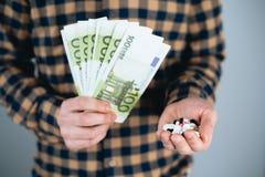 Pieniądze i pigułki w ręce, Wydaje zbyt dużo pieniądze na lekach Pojęcie nałóg zdjęcie royalty free