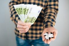 Pieniądze i pigułki w ręce, Wydaje zbyt dużo pieniądze na lekach Pojęcie nałóg obrazy stock