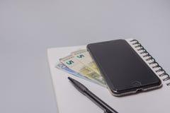 Pieniądze, mądrze telefon, pióro i notatnik na biurowym stole na białym tle, budżeta burlap monet pojęcia dziura jadący worek roz Obraz Stock
