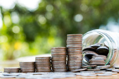 Pieniądze monety sterty narastający wykres z mony słojem Obrazy Stock