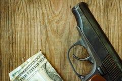 Pieniądze na drewnianym stole i pistolet zdjęcie stock