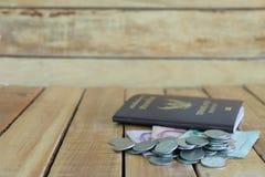 Pieniądze oszczędzania pojęcie dla wakacje z monety stertą i paszport na drewnianych tło, zdjęcie royalty free