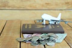 Pieniądze oszczędzania pojęcie dla wakacje z monety stertą, paszportem i samolot zabawką na drewnianych tło, zdjęcie stock