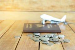 Pieniądze oszczędzania pojęcie dla wakacje z monety stertą, paszportem i samolot zabawką na drewnianych tło, obrazy stock