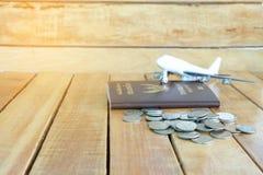 Pieniądze oszczędzania pojęcie dla wakacje z monety stertą, paszportem i samolot zabawką na drewnianych tło, zdjęcia royalty free