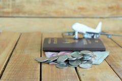 Pieniądze oszczędzania pojęcie dla wakacje z monety stertą, paszportem i samolot zabawką na drewnianych tło, obraz royalty free