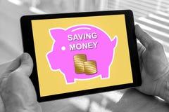 Pieniądze oszczędzania pojęcie na pastylce zdjęcie stock