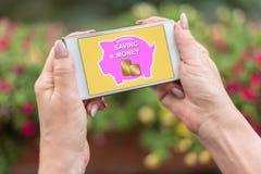 Pieniądze oszczędzania pojęcie na smartphone zdjęcia stock
