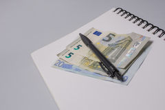 Pieniądze, pióro i notatnik na biurowym stole na białym tle, budżeta burlap monet pojęcia dziura jadący worek rozlewający Obraz Stock
