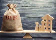 Pieniądze torba z słowo długiem i miniaturowy dom z rodziną na skalach Zapłata dług dla nieruchomości Płaci daleko obrazy royalty free