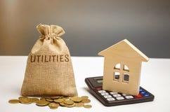 Pieniądze torba z słowo użyteczność i drewnianym domem Pojęcie oszczędzanie pieniądze dla zapłaty użyteczność Akumulacja zdjęcia royalty free