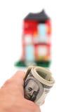 Pieniądze w ręce na tle domy obraz stock