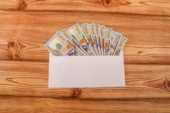 Pieniądze w wyznaniach 100 dolarów w białej kopercie na drewnianym stole fotografia stock