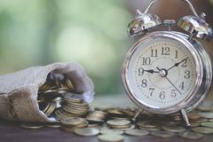 Pieniądze zegar na drewnianym stole z natury tłem i torby, pieniędzy oszczędzania, Broguje r monetę, Ratują pieniądze dla przyszł zdjęcia stock