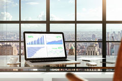 Pieniężne statystyki na laptopu ekranie na szklistym stole w nowożytnym zdjęcia royalty free