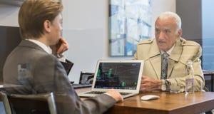 Pieniężnego advisor ordynacyjny starszy klient z jego strategią inwestycyjną zdjęcia royalty free