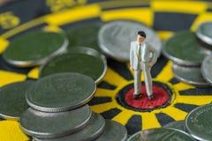 Pieniężny biznesowy pojęcie jako miniaturowa biznesowego mężczyzna pozycja przy Zdjęcie Stock