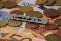 pieniężny kapitalizm - słowo drukował na metalu barze metalu bar umieszczał na kilka banknotach obrazy stock