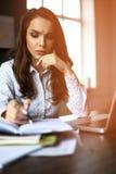 Pieniężny kierownik bierze notatki gdy pracujący dalej Zdjęcie Stock