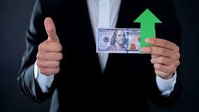 Pieniężny konsultant z dolarowymi banknotami pokazuje aprobaty i zieloną strzałę obraz stock
