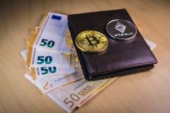 Pieniężny pojęcie z fizycznym bitcoin i ethereum nad portflem z Euro rachunkami zdjęcia stock
