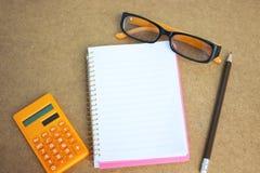 Pieniężny pojęcie z notatnikiem, eyeglass i kalkulatorem na drewnianym tle, Fotografia Stock