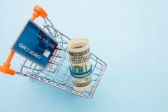 Pieniędzy dolary staczający się w kredytową kartę w miniaturowym wózek na zakupy i tubkę fotografia stock