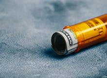 Pieniędzy rachunki w pomarańczowej pigułki butelce na stołowym tle medyczny pojęcie z kopią Zdjęcia Royalty Free