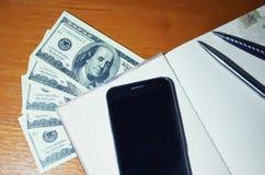 Pieniądze, smartphone i notepad, Zdjęcia Stock