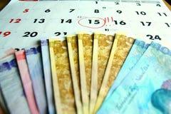 Pieniędzy rachunki na kalendarzu Obrazy Royalty Free