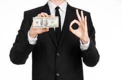 Pieniądze i biznesu temat: mężczyzna trzyma rachunek 100 dolarów w czarnym kostiumu i uwypukla ręka gest na odosobnionym bielu ba Zdjęcie Stock