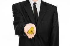 Pieniądze i biznesu temat: mężczyzna trzyma stos odizolowywający złociste monety w studiu na białym tle w czarnym kostiumu Obraz Stock
