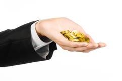 Pieniądze i biznesu temat: wręcza w czarnym kostiumu trzyma stos odizolowywający złociste monety w studiu na białym tle Zdjęcia Stock