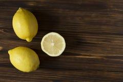 In pieno e metà del limone sulla tavola di legno marrone Immagine Stock