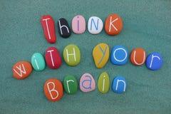 Piense con su cerebro, mensaje de la sugerencia compuesto con las piedras coloreadas multi del mar sobre la arena verde ilustración del vector