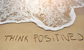 Piense el positivo escrito en la playa de la arena - concepto de pensamiento positivo Fotos de archivo libres de regalías