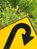 Piense el verde - roadsign del giro de 180 grados en la vegetación enorme Foto de archivo libre de regalías