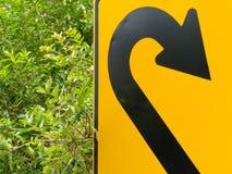 Piense el verde - roadsign del giro de 180 grados en la vegetación enorme Fotos de archivo