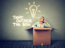 Piense fuera del rectángulo Mujer que sale de la caja con gran idea fotografía de archivo libre de regalías