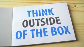 Piense fuera en de la caja en la página del cuaderno metrajes