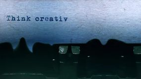 Piense mecanografiar creativo de la palabra centrado en la hoja de papel en viejo audio de la máquina de escribir