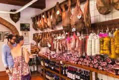 Pienza, †«22-ое июля 2017 Италии: Неопознанные мясные продукты приобретений женщины и человека традиционные итальянские Стоковые Фото