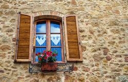 Pienza, Italy – July 22, 2017: Typical italian window with shutters on a stone wall in the ancient Tuscany town Pienza. Window in the home with flower pot Royalty Free Stock Image