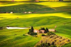 Pienza, ländliche Sonnenunterganglandschaft. Landschaftsbauernhof und grünes Feld Lizenzfreie Stockbilder