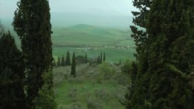 Pienza, view of the Chianti hills among the cypress trees with rain and mist. stock footage