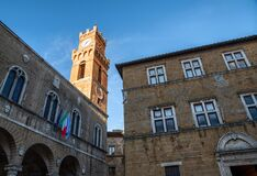 Pienza, Tuscany, Italy. August 2020. The late afternoon sun illuminates the clock tower in the historic center with warm light.