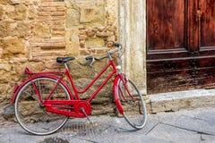 PIENZA, TUSCANY/ITALY - 19 DE MAIO: Bicicleta vermelha que inclina-se contra um w Fotografia de Stock